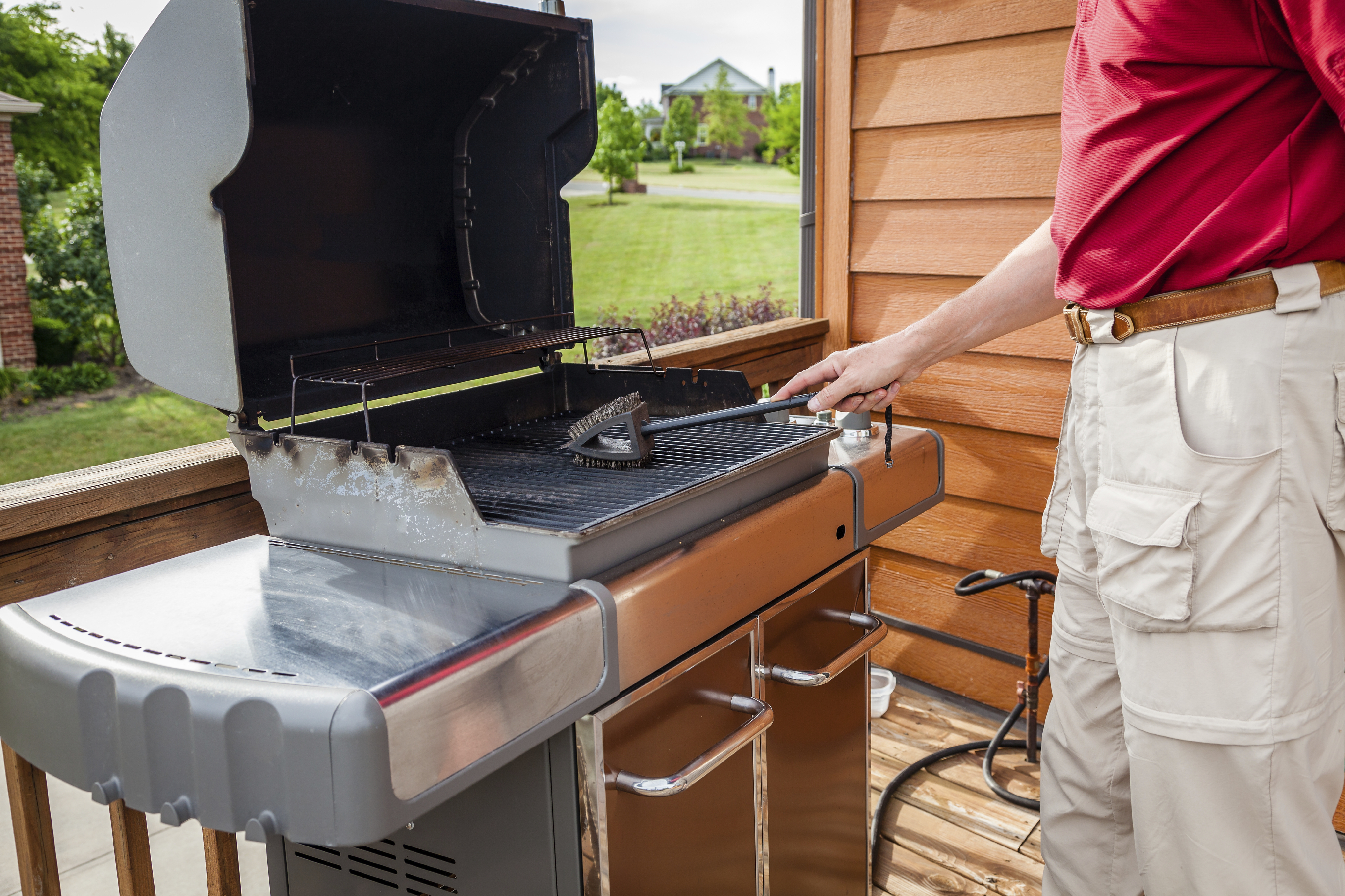 Man Cleaning grill with a wire brush