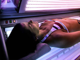 a woman lies in a tanning booth