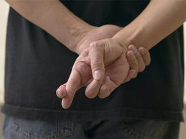 Close up of man crossing fingers behind back.
