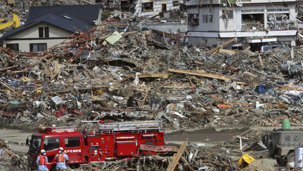 Fire fighters search for survivors following the March 11 earthquake and tsunami in Rikuzentakata, Iwate prefecture, northeastern Japan, Friday, March 18, 2011.(AP Photo/Koji Sasahara)