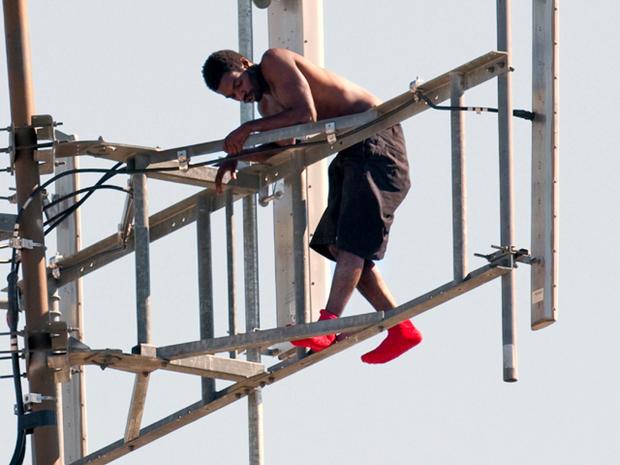 在2011年8月14日,在俄克拉荷马州塔尔萨,一名警察与一只脚踩在一根支撑梁上,与警察对峙,重新安排在一座通讯塔上。