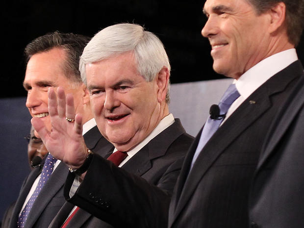 Republican presidential candidates (L-R) former Massachusetts Governor Mitt Romney, former Speaker of the House Newt Gingrich (R-GA), and Texas Governor Rick Perry acknowledge audience prior to a presidential debate at Wofford College November 12, 2011 in Spartanburg, South Carolina. The debate was focused on national security and foreign policy.