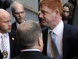Penn State assistant football coach Mike McQueary, right, arrives at Dauphin County Court surrounded by heavy security Friday, Dec 16, 2011, in Harrisburg, Pa.