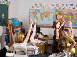 Rear view of schoolboy in classroom with hands raised