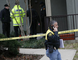 Grapevine police investigate the scene where they found seven people dead outside Dallas in Grapevine, Texas, Sunday, Dec. 25, 2011. Four women and three men who police believe to be related were found apparently shot to death, and authorities said they believe the shooter is among the dead.