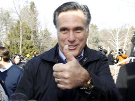 Former Massachusetts Gov. Mitt Romney gives a thumbs up as he campaigns on primary day outside a polling station at Webster School in Manchester, N.H., Jan. 10, 2012.