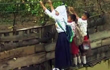 Indonesian students cross collapsed bridge