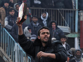 demonstrator holds a copy of a half-burnt Koran
