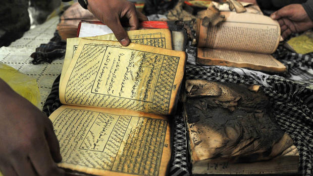 Afghan demonstrators show copies of Koran books allegedly set alight by U.S. soldiers.