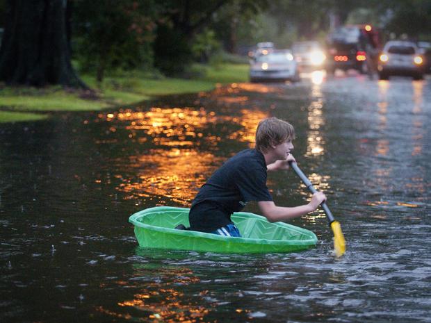杰克逊维尔12岁的Mac Lyerly微笑着划着Avondale大道上的一个小型塑料游泳池,随着北佛罗里达州居民应对2012年6月26日星期二热带风暴Debby正在进行的降雨,雨水总量继续增加。