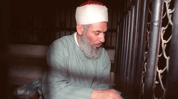 """""""Blind Sheik"""" Omar Ahmad Rahman sits and prays inside an iron cage at the opening of court session in Cairo Aug. 6, 1989."""