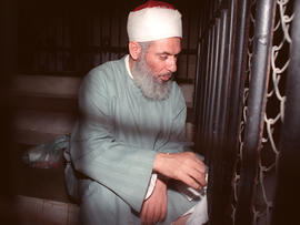 Blind sheik Omar Abdel-Rahman sits and prays inside an iron cage at the opening of court session in Cairo Aug. 6, 1989.