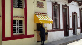 A customer picks up take-out food sold out of a private home's front door in Havana.