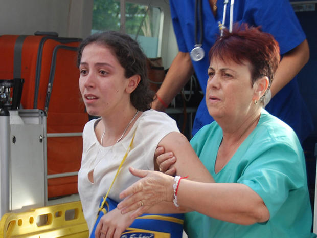 Unidentified Israeli tourist is helped as she arrives to Bourgas hospital after a bus carrying Israeli tourists in the Bulgarian resort city of Bourgas exploded Wednesday.