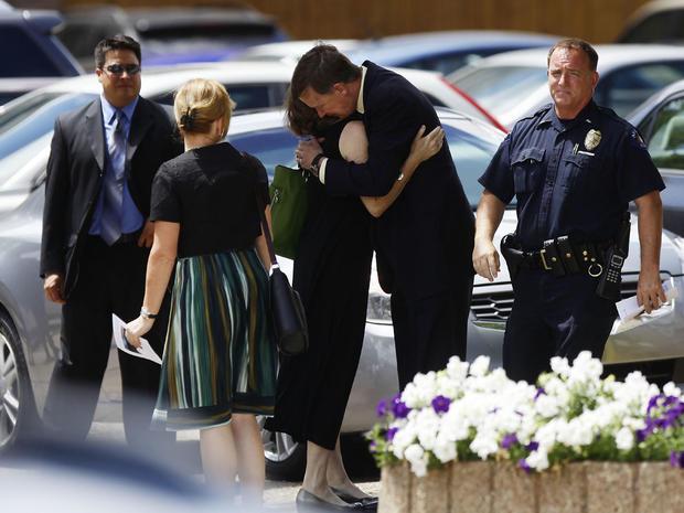 科罗拉多州州长John Hickenlooper(第3 R)在2012年7月25日在科罗拉多州丹佛市的Pathways教堂离开追悼会他们的Gordon Cowden后,拥抱了他的妻子Helen Thorpe。