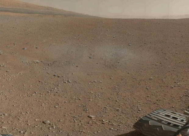 Scorch marks left by Curiosity's landing rockets are clearly visible in the color image that also shows the rim of Gale Crater.