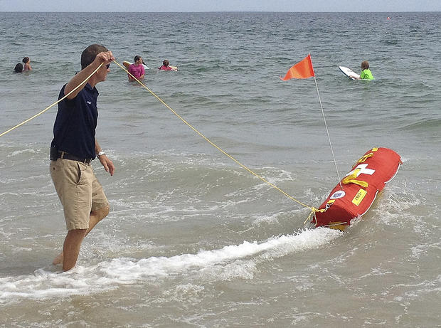 Fire Chief Louis Misto holds a line attached to the EMILY remote-control lifesaving device as it propels itself in the water and away from the shore at Old Town Beach, in Westerly, R.I.