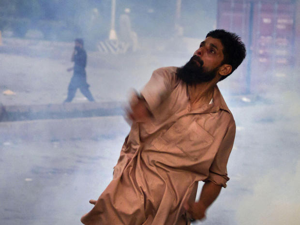 A Pakistani protester hurls back a tear gas canister fired by police, as another protester talks on a cell phone in the background