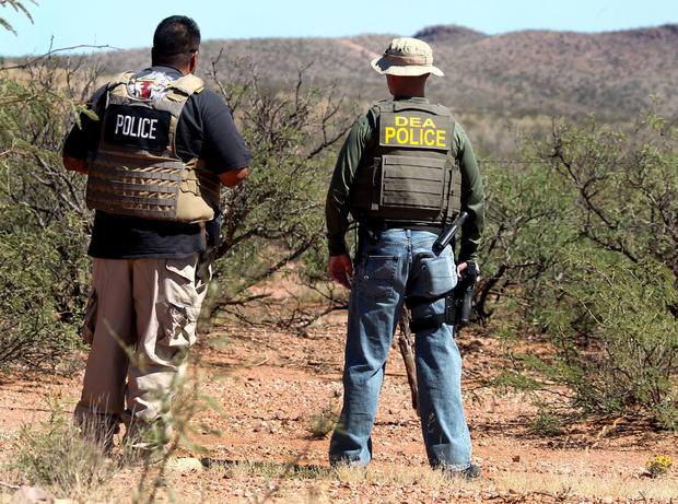 Det. Bill Silva, left, with the Bisbee Police Department, and an unnamed agent with the Drug Enforcement Administration patrol a fence line east of Naco, Ariz., after a Border Patrol agent was killed early Tuesday, Oct. 2, 2012.