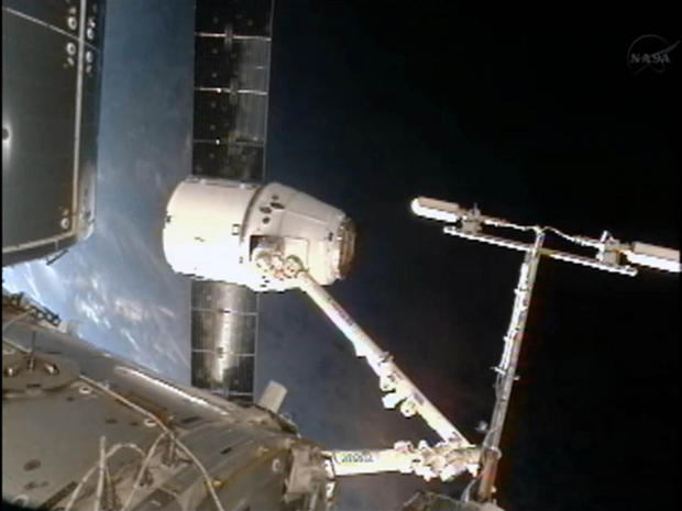 The blue Earth glows behind SpaceX's private Dragon spacecraft as it sits at the end of the International Space Station's robotic arm following its arrival on Oct. 10, 2012.