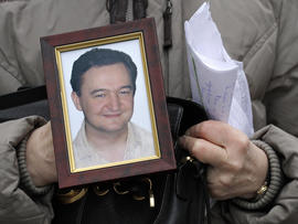 A portrait of lawyer Sergei Magnitsky who died in jail, is held by his mother Nataliya Magnitskaya
