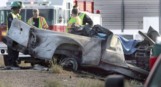 紧急救援人员旁边是一辆被烧毁的卡车,该卡车在10号州际公路的西边车道向东行驶,并于2012年11月20日在亚利桑那州卡萨格兰德撞上了Tuseday旅游巴士。