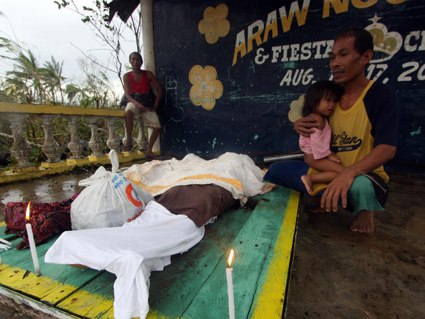 A man looks at the dead bodies of relatives killed by landslides after Typhoon Bopha