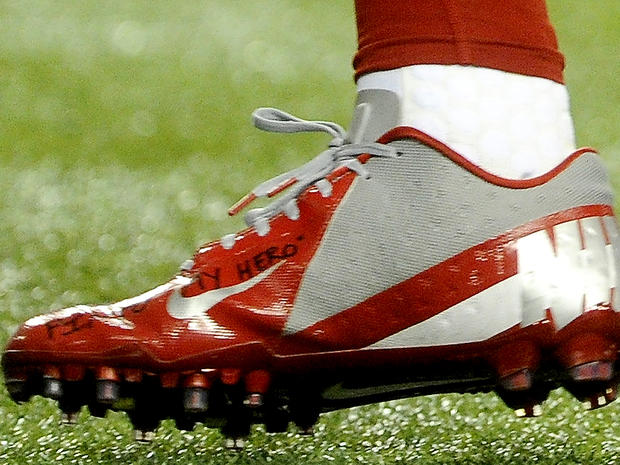 in this Sunday, Dec. 16, 2012, photo, a shoe worn by New York Giants wide receiver Victor Cruz bears a message dedicated to 6-year-old Jack Pinto, one of the victims in last week's school shootings at Sandy Hook Elementary School in Newtown, Conn., as Cruz warms up for the Giants' NFL football game against the Atlanta Falcons in Atlanta.
