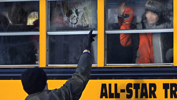 A man waves to a child on a bus on the first day of classes after the holiday break, in Newtown, Conn.,Wednesday, Jan. 2, 2013.
