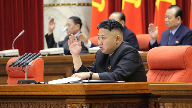 In this Sunday, March 31, 2013 photo released by the Korean Central News Agency (KCNA) and distributed in Tokyo Monday, April 1, 2013 by the Korea News Service, North Korean leader Kim Jong Un raises his hand with other officials to adopt a statement during a plenary meeting of the central committee of the ruling Workers' Party in Pyongyang, North Korea.