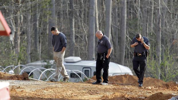 2013年4月8日星期一,一名男子在调查人员的陪同下,在一个倒塌的建筑工地现场周围,周日在纽约州斯坦利的Cedarbrook Court,当两面儿童的土墙倒塌时,两名儿童死亡。