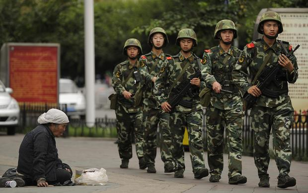 A Muslim Uighur woman begs as armed Chinese paramilitary police march past on a street in Urumqi, the capital of the Xinjiang region