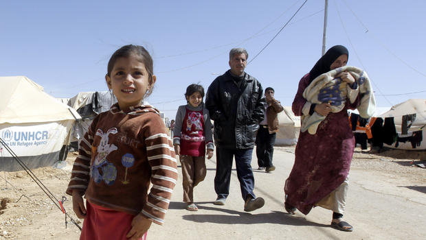 A Syrian family walks amid tents at the Zaatari refugee camp