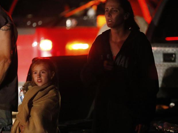 七岁的卡特里娜·阿什(Katrina Ash)和她的母亲安伯特·阿什(Amber Ash)一起看着重型设备进入龙卷风受损的街区