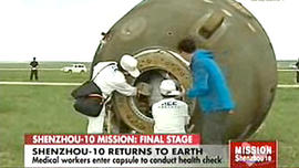 Crew attends to the recently landed Shenzhou 10 spacecraft, carrying three astronauts, as seen on Chinese television on June 25, 2013.