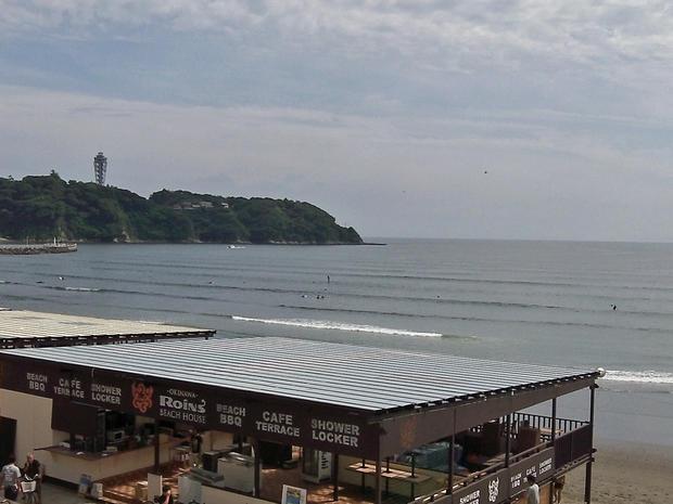 Windsurfers enjoy the early summer waves in the Japanese beach resort of Enoshima