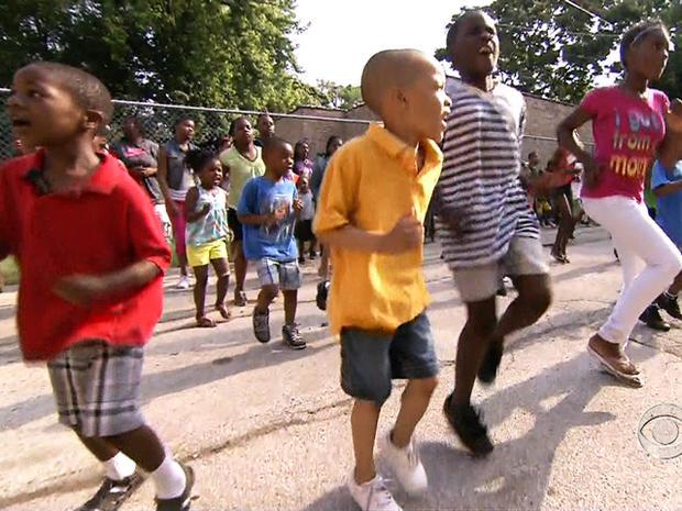 孩子们在芝加哥新山Cal髅教堂的夏令营的黑顶操场上玩耍。