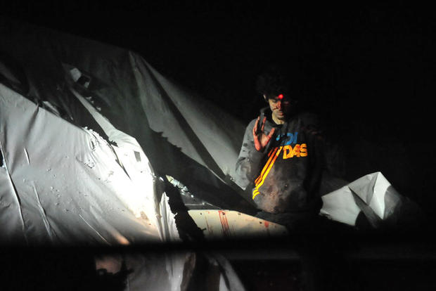 Dzhokhar Tsarnaev emerges from a boat he was hiding in in Watertown, Mass., following a nearly 24-hour-long manhunt with authorities on April 19, 2013.