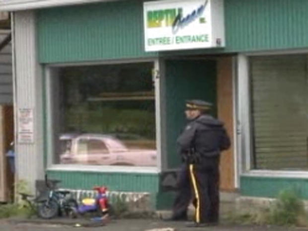 Police stand in front of Reptile Ocean pet store in New Brunswick, Canada on Aug. 5, 2013, after two young boys were strangled as they slept by a python that escaped the store and apparently slithered through the ventilation system into the apartment above. Their tricycles can be seen at bottom left.