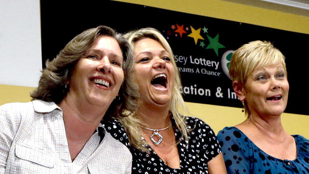 Lottery winners Lisa K. Presutto, left, Darlene M. Riccio, second left and Barbara Jo Riivald, third right, share a laugh as they listen to Lottery Director Carole Hedinger, right, executive director of the New Jersey lottery Tuesday, Aug. 13, 2013, in Toms River, N.J.
