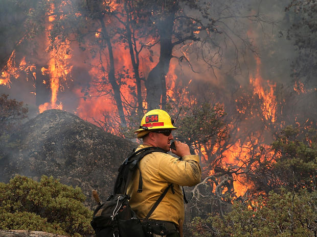 U.S. Forest Service firefighter Chris Brossard talks on his radio while monitoring a spot fire while battling the Rim Fire Aug. 24, 2013, in Yosemite National Park, Calif.