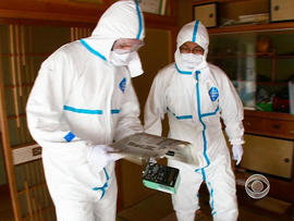 Akira Okawara and Seth Doane wear protective suits to travel to Okuma.