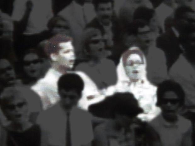 """一个年轻的朱利安邦德和一个年轻的玛丽安赖特唱着""""我们要克服。"""""""