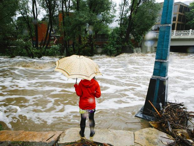 2013年9月12日,在科罗拉多州博尔德市遭受三天强降雨后,一名妇女看着博尔德溪被淹。