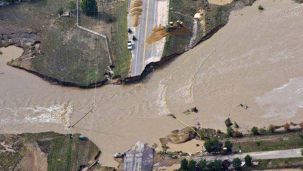 2013年9月14日星期六,格里利附近科罗拉多州韦尔德县南普拉特河沿岸的一条公路工作人员在一条公路上工作。该地区的数百条道路被洪水淹没或毁坏。受影响的面积为4500平方英里。