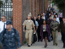 Military personnel and workers walk along the perimeter of the Washington Navy Yard Sept. 19, 2013.