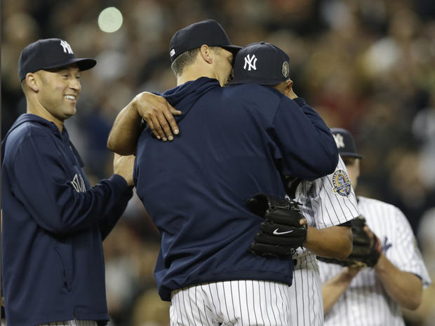 New York Yankees shortstop Derek Jeter, left, watches as starting pitcher Andy Pettitte, center, embraces a sobbing Mariano Rivera on the mound in the ninth inning of Rivera's final appearance in a game at Yankee Stadium, against the Tampa Bay Rays on Sept. 26, 2013. The Rays won, 4-0.