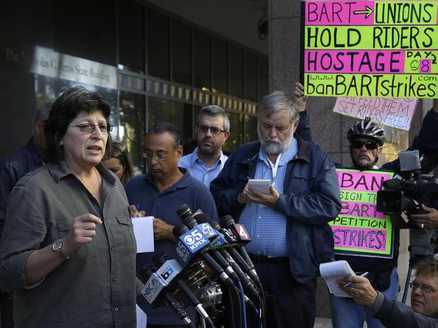 Roxanne Sanchez,左,服务员工国际联盟当地1021主席,在新闻发布会上发言