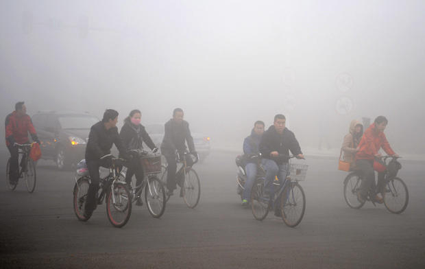 Cyclists ride along a road as heavy fog engulfs Daqing, China.
