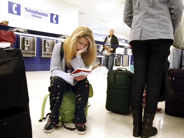 18岁的Jamie Collier在2013年11月26日在北卡罗来纳州罗利市中心的Raleigh Greyhound车站等车登机时全神贯注于她的书。